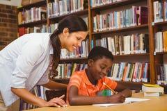 Professor que ajuda ao menino com trabalhos de casa na biblioteca Imagens de Stock Royalty Free