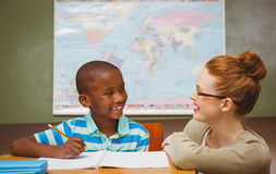 Professor que ajuda ao rapaz pequeno com trabalhos de casa na sala de aula imagem de stock