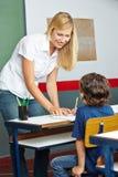 Professor que ajuda o estudante da escola primária fotografia de stock