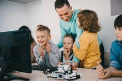 professor que ajuda seus estudantes adolescentes com o robô diy na haste fotografia de stock royalty free