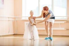 Professor que ajusta a posição de bailarinas novas na barra Fotos de Stock Royalty Free