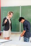 Professor que critica um aluno na turma escolar Imagens de Stock Royalty Free