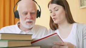 Professor que dá a lição de escuta ao estudante superior Tutor que explica a pronunciação da língua estrangeira video estoque