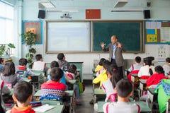 Professor que dá uma lição às crianças em uma sala de aula chinesa Imagens de Stock
