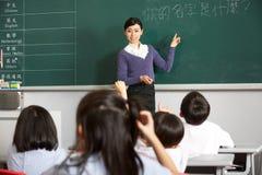 Professor que está pela escola do chinês de Quadro-negro  foto de stock