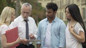 Professor que explica como redigir a pesquisa científica, mostrando exemplos na tabuleta filme