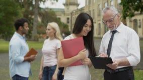 Professor que fala com o estudante asiático, discutindo o projeto da ciência no terreno filme
