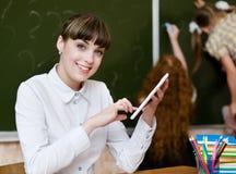 Professor que guarda um tablet pc na sala de aula olhando o camer Fotografia de Stock Royalty Free