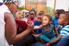 Professor que lê um livro com uma classe de crianças prées-escolar