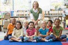 Professor que senta-se com as crianças na biblioteca