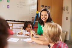 Professor que senta-se com as crianças na lição da escola primária Fotos de Stock