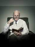 Professor reading in armchair Royalty Free Stock Photos