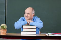 Professor Relaxing On Stacked Books At Desk Stock Photography