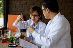 Scientist test chimcal liquid in lab. Professor scientist consult his partner about liquid substance in test tube at scientific chemical lab room. Science and Royalty Free Stock Image