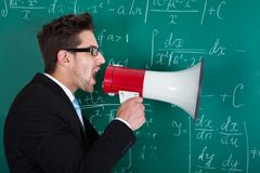 Professor screaming on megaphone against blackboard Royalty Free Stock Photography