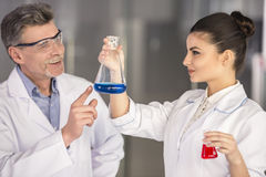 Professor. Senior chemistry professor and his assistant working in laboratory royalty free stock image