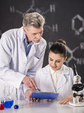 Professor. Senior chemistry professor and his assistant working  in  laboratory Stock Images