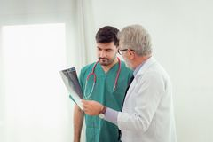 Professor senior doctor explaining case study to assistance abou. T method patient treatment with mammogram film x-ray of patient `s head royalty free stock image