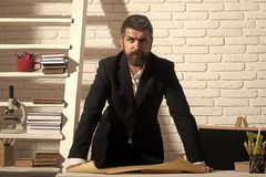 Professor with serious face expression stands by desk with paper. Man with beard on white brick wall background. Teacher and school supplies in classroom stock photography