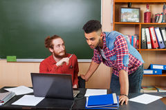 Professor Show Laptop Computer To Young Hispanic Student, University Teacher Discussion. With Pupil In Classroom Stock Photography