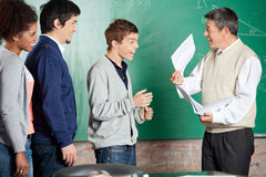 Professor Showing Test Result To Successful. Happy male professor showing test result to successful male student in classroom royalty free stock photography