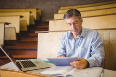 Professor sitting at desk using digital tablet stock photo