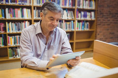 Professor sitting at desk using digital tablet. In college library royalty free stock images