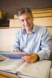 Professor sitting at desk using digital tablet Royalty Free Stock Photography