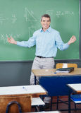 Professor Standing Arms Outstretched Against Board Stock Photography