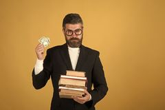 Professor with strict face expression. Teacher holds pile of books. And money. Teaching and knowledge concept. Man with beard on yellow background, copy space royalty free stock photography
