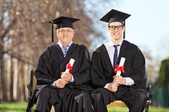 Professor and student posing on a bench outdoors Royalty Free Stock Photography