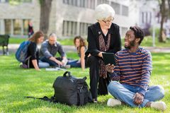 Professor and Student Working Together Outdoors. University Professor assisting grad student with small digital tablet Stock Photography