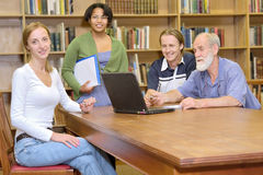 Professor with students. Multiracial group of four friendly people studying in library. Shot in South Africa royalty free stock photo