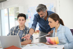 Professor with students in architecture school stock image