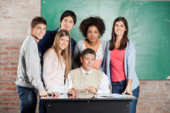 Professor And Students At Desk Against Greenboard. Portrait of confident male professor and students at desk against greenboard in classroom royalty free stock photos
