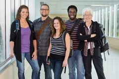 Professor with Students. Group portrait of confident multiethnic university students standing in corridor with professor Stock Photos