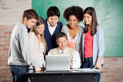 Professor And Students Looking At Laptop In. Mature male professor and students looking at laptop in classroom Royalty Free Stock Photo