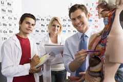 Professor With Students In Science Class. Portrait of a happy professor and students with anatomical model in science class Royalty Free Stock Photography