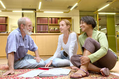 Professor with students sit on carpet Stock Images