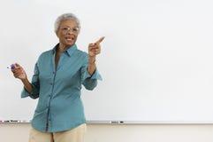Professor superior que aponta ao gesticular contra a placa branca na sala de aula imagem de stock