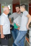 Professor talking to two students in corridor. Students royalty free stock images