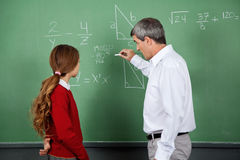 Professor Teaching Mathematics To Female Student. Side view of male professor teaching mathematics to female student on board in classroom Stock Photography
