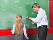 Professor Teaching Mathematics To Little Girl On. Side view of mature professor teaching mathematics to little girl on board at classroom Stock Photos