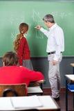 Professor Teaching Mathematics To Teenage. Mature male professor teaching mathematics to teenage schoolgirl in classroom Stock Photography