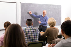Professor teaching people at courses. Professor teaching different age students at extension courses royalty free stock photo