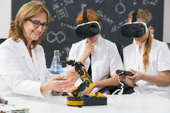 Professor and two science students wearing VR goggles Stock Photography