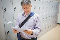 Professor using digital tablet in locker room Royalty Free Stock Images