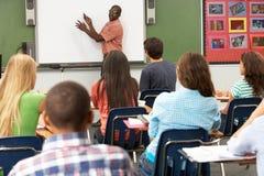 Professor Using Interactive Whiteboard durante a lição Fotos de Stock Royalty Free