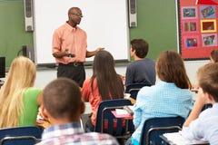 Professor Using Interactive Whiteboard durante a lição Fotografia de Stock Royalty Free