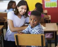 Professor voluntário da fêmea e menino da escola primária que sorri à câmera foto de stock
